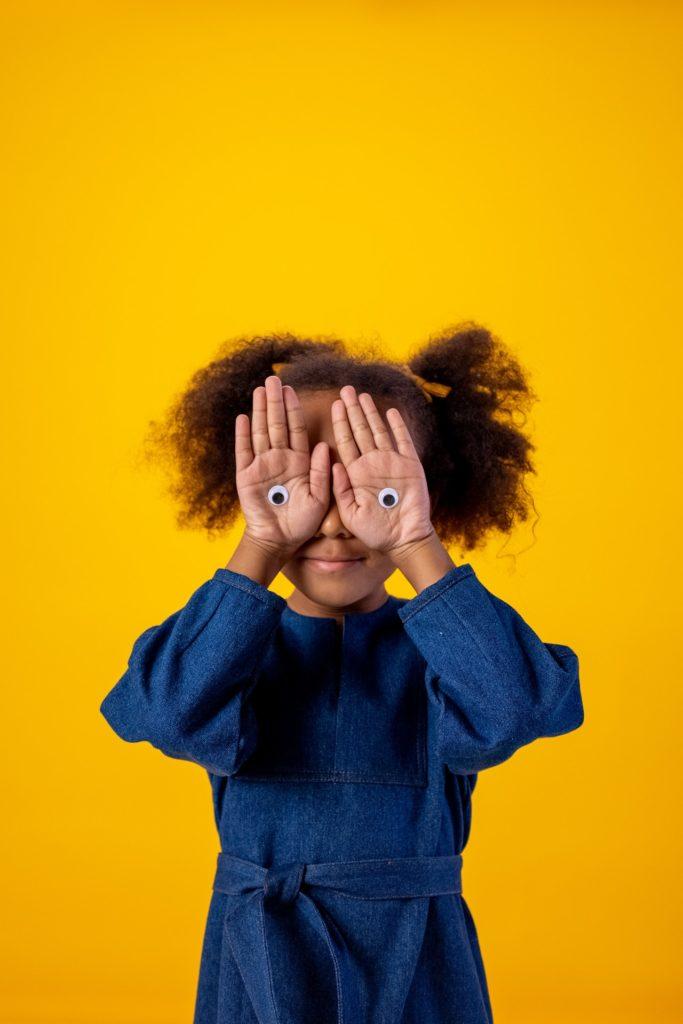 Ein Kinderfoto eines jungen Mädchens vor gelbem Hintergrund
