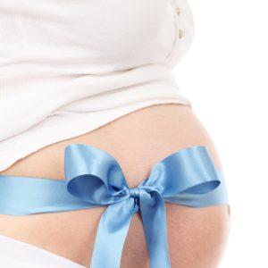 Eine schwangere Frau mit Schleife um den Bauch