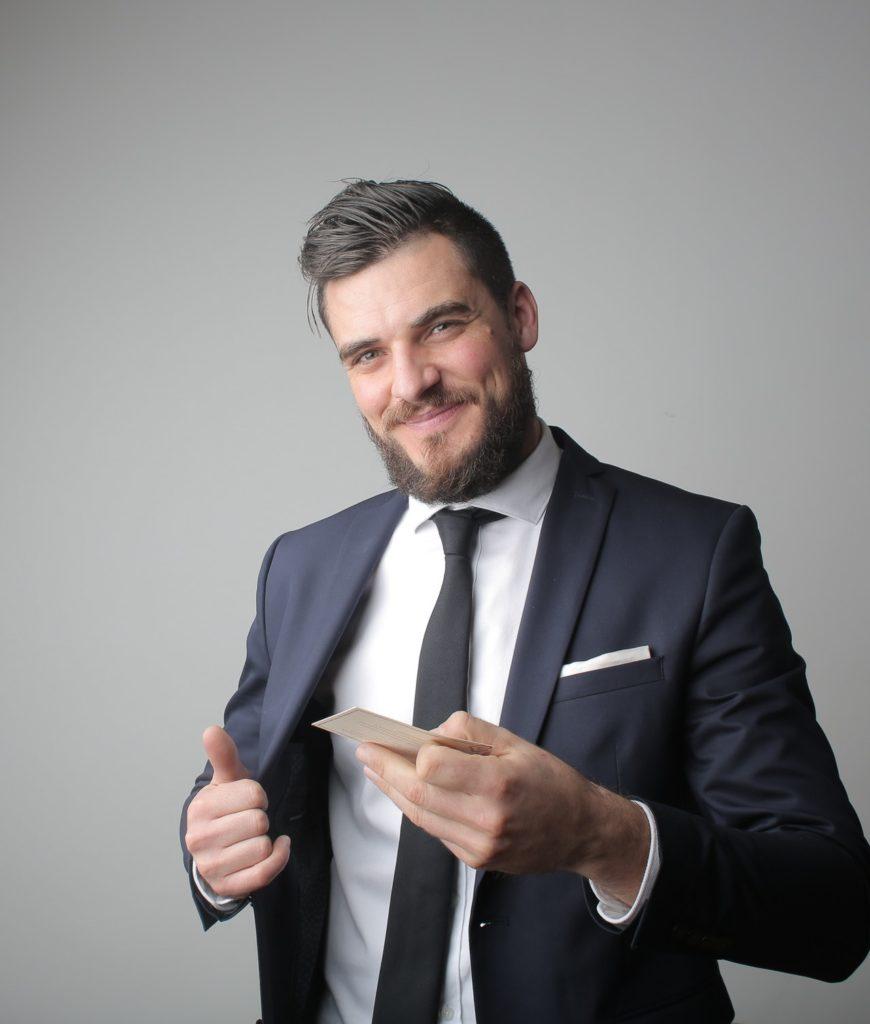 Bewerbungsfoto - Junger Mann hält eine Visitenkarte in Richtung Kamera