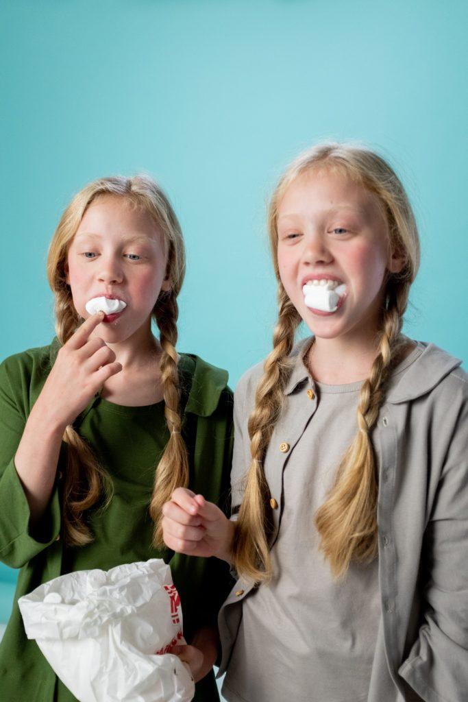 Kinderfotoshooting mit zwei Mädchen, die Marshmallows essen