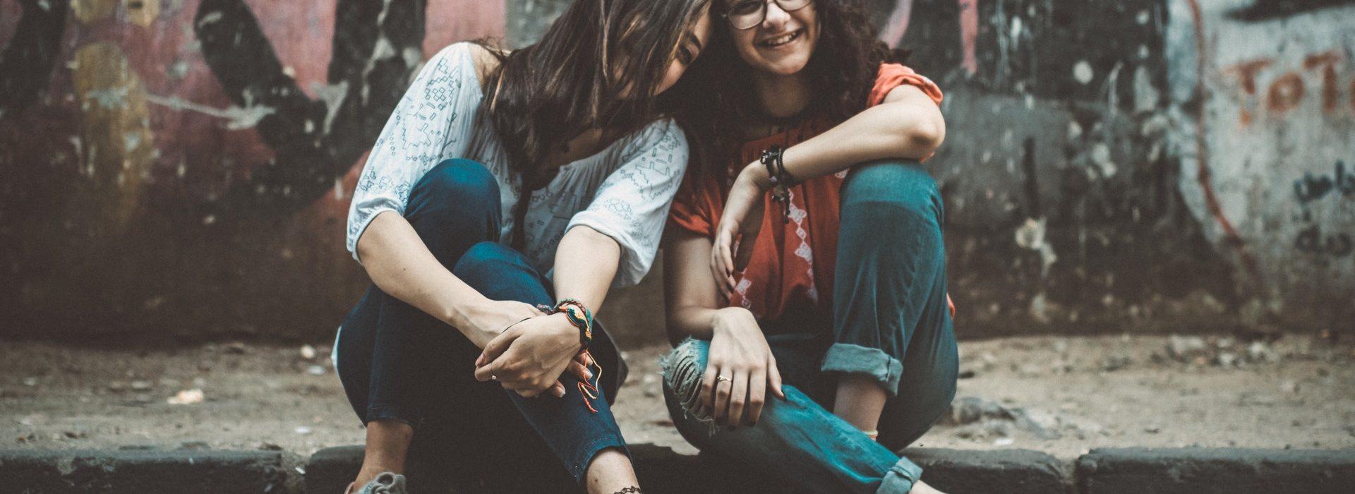 Zwei Frauen sitzen in einer Urban Kulisse vor Graffiti